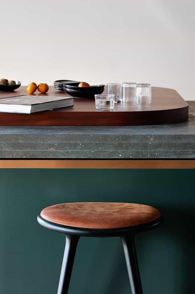 Un plan original composé de bois cintré, de pierre gris Saint-Vincent, d'un liseré en cuivre et d'un laquage vert. Tabouret (Mater)