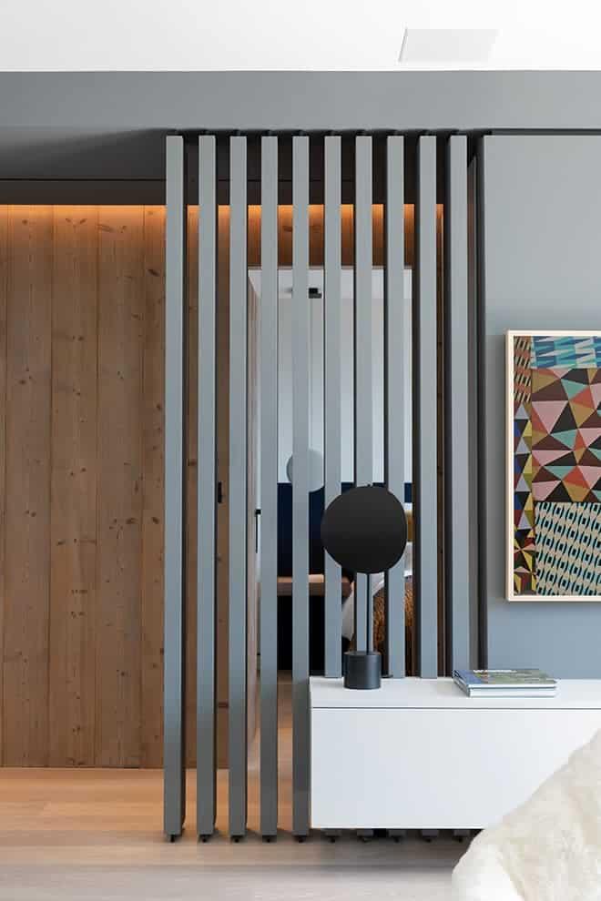 Derrière la claire-voie et le meuble en porte-à-faux laqués sans fixations apparentes, se cachent la chambre d'amis et l'escalier