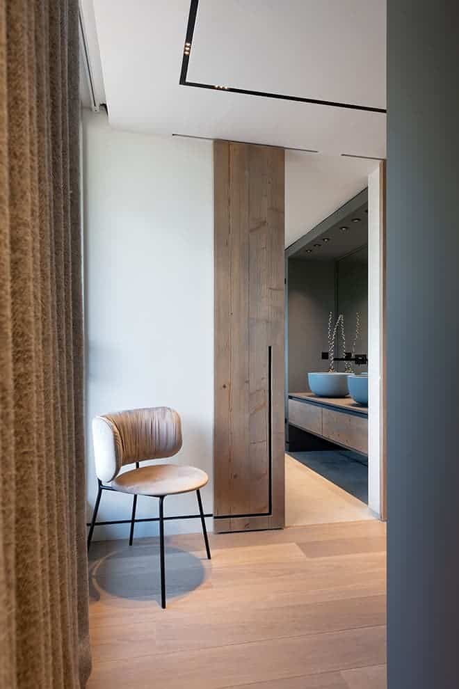 Espace de circulation de la master suite, menant à la salle de bains et au dressing. Chaise (Bolia)