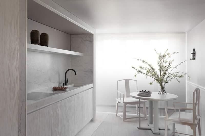 """La cuisine en frêne brossé teinté """"craie"""" reprend les codes précédents, affinant le veinage du marbre sélectionné avec soin"""