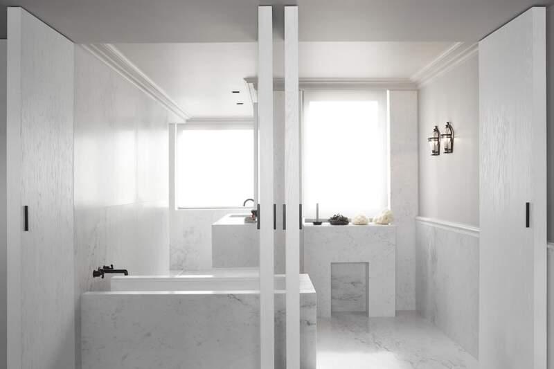La salle de bains impose une radicalité adoucie par les portes pivot en frêne brossé