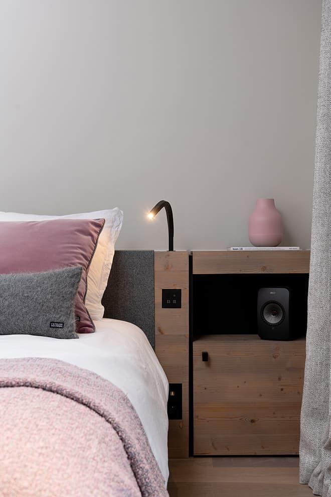 Tête de lit de la master suite en épicéa verni, desssinée par By. Lit (Lago). Liseuse (Linea Light). Système Hi-Fi (Kev)
