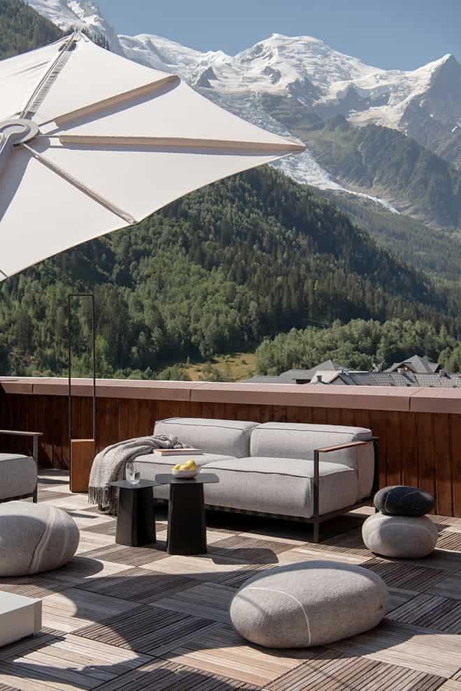 Vue à 360° sur les toits chamoniards et les massifs. Parasol (Umbrosa). Galets (Fivetimesone). Canapé et lampe (Talenti). Tables (Vitra)