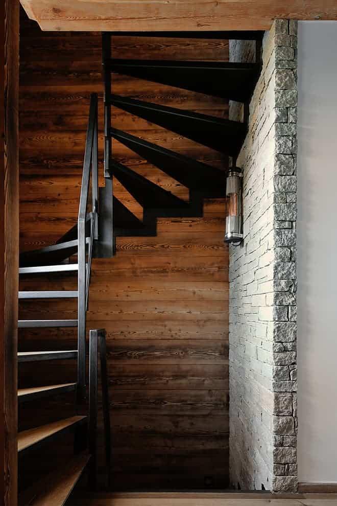 Escalier graphique contemporain souligné par un mur en pierre de Luzerne, reliant les étages. Applique (DCW Éditions)