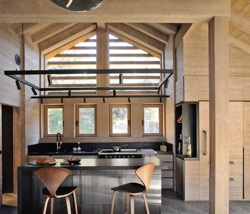 Espace cuisine reprenant l'habillage métallique de la cheminée. Rails architecturaux (Flos). Tabourets bar (Cherner)