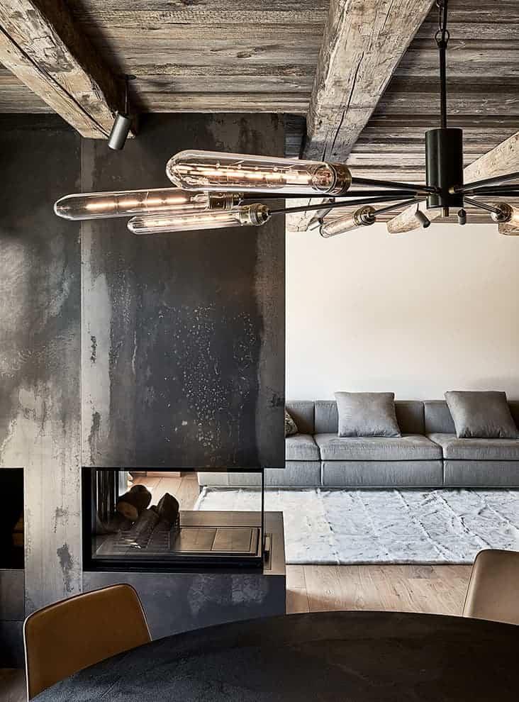 La cheminée géométrique, en métal gravé et verre croise le regard de la salle à manger et du salon
