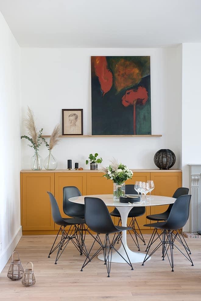 Lovée dans un coin, la scène repas se nuancent de chromatiques chaleureuses. Table (Knoll). Chaises (Vitra). Composition florale (Clesa Fleurs & Jardin). Agencement intégré dessiné par l'Agence Del-In