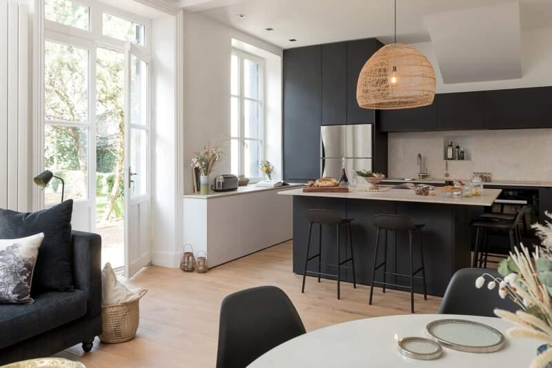 Reconnectée avec le jardin et la notion de partage, la pièce de jour donne la part belle à la cuisine sur-mesure, en laque noire mate. Tabourets (Normann Copenhagen)