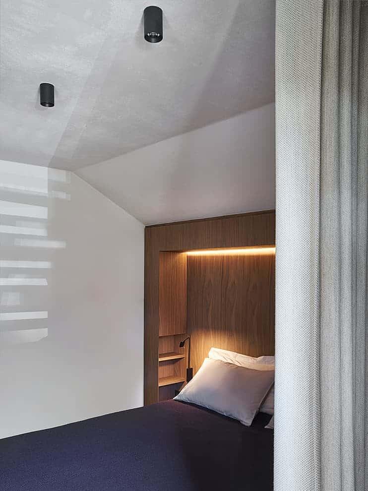 Suite invitée focalisée sur le lit. Rideaux (Ivano Redaelli)