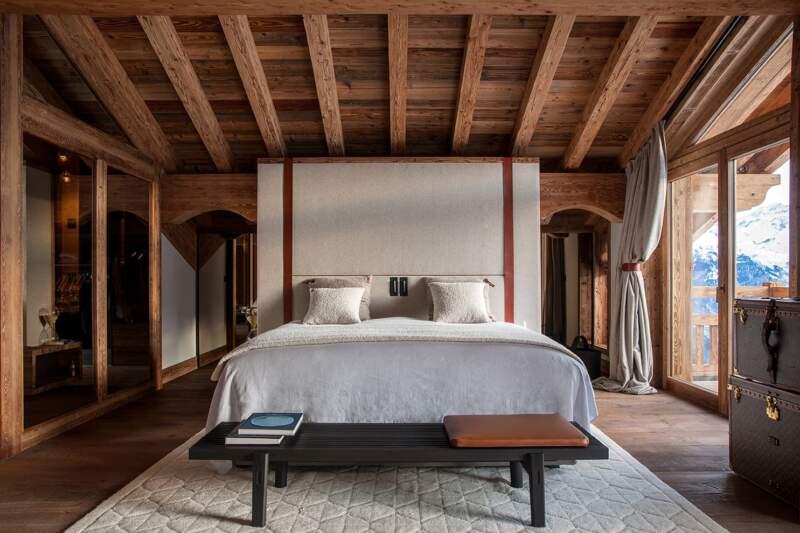 Au sommet du chalet, la suite parentale reprenant dans sa conception le dessin des malles Louis Vuitton. Tête de lit (Arpin). Liseuse (Marset). Tapis tibétain (L'Atelier des Frères)