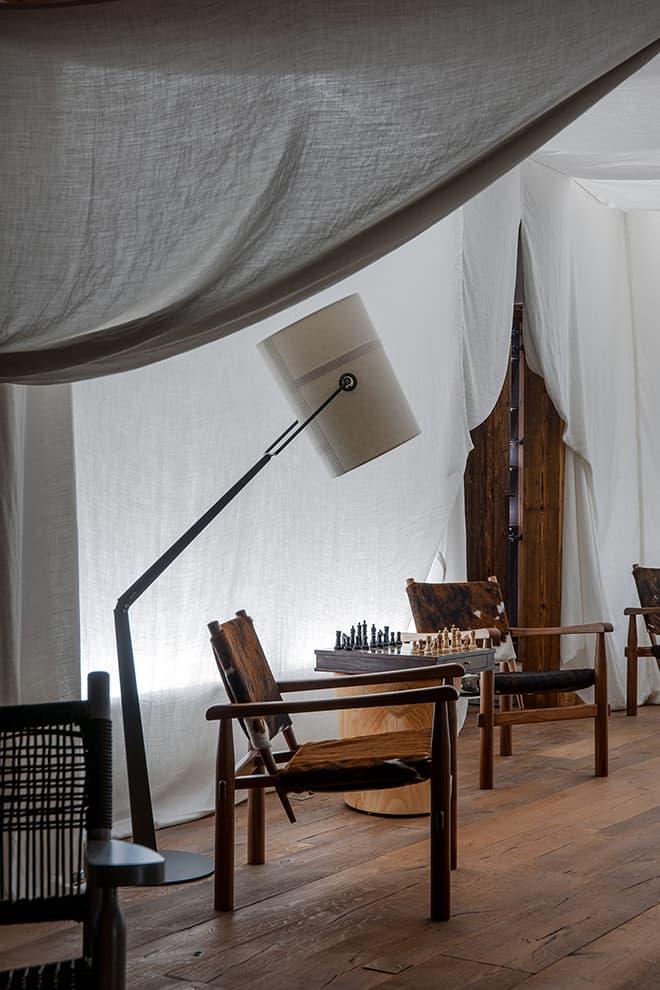 Espace loisirs sous un voile de lin imaginé comme un abat-jour grandeur nature. Lampe (Diesel with Foscarini). Fauteuils (Cassina)