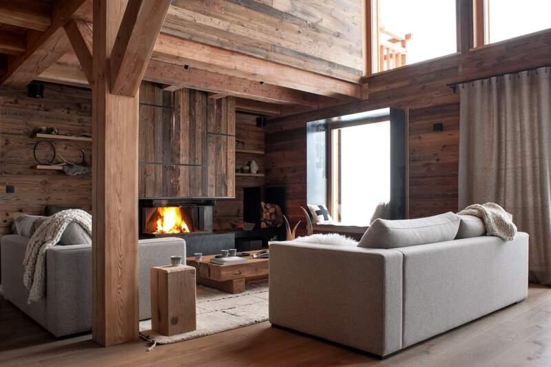 Le salon donnant sur la master suite. Cheminée en vieux bois insertions métal. Canapés sur-mesure et rideaux (Arpin Megève)