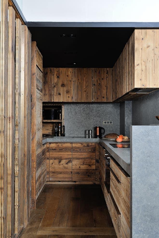 Lovée sous la mezzanine, la cuisine fonctionnelle reprend la trame bois, bronze et pierre. Appareillage (Meljac)