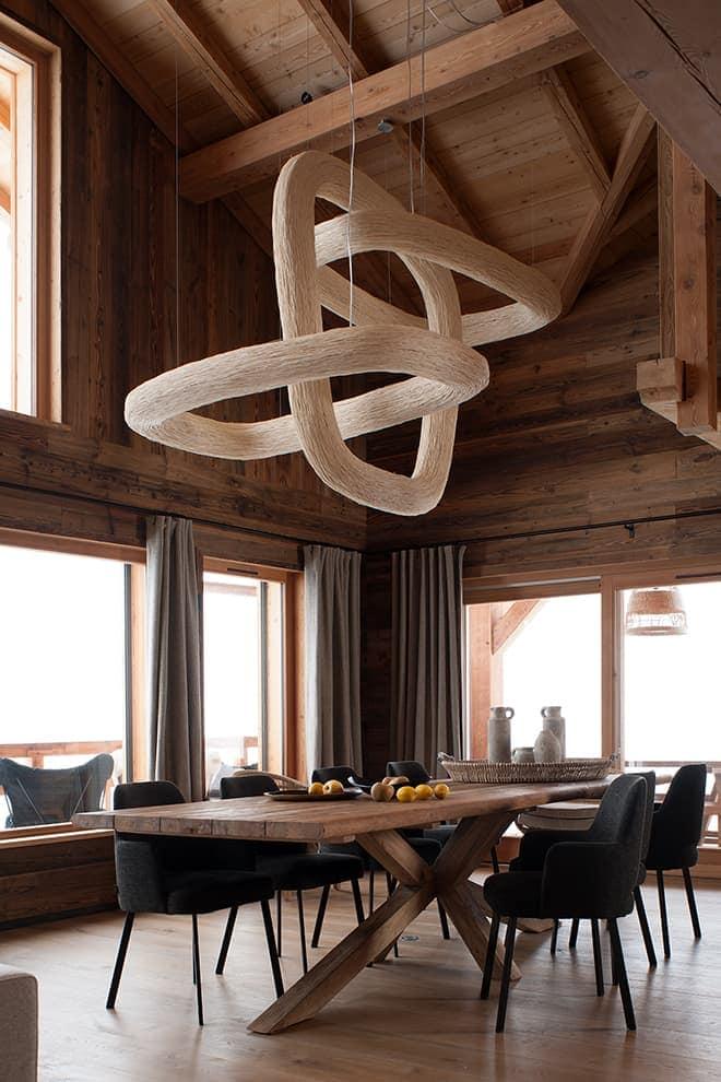 Salle à manger cathédrale. Suspension de 1,20 x 2,50 mètres (Ango). Table en teck et fauteuils en laine chinés sur Maison&Objet