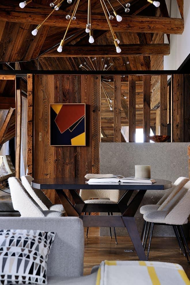 Salle à manger reliée à la cuisine et rythmée par le jeu de miroirs gommant les retombées sous plafond