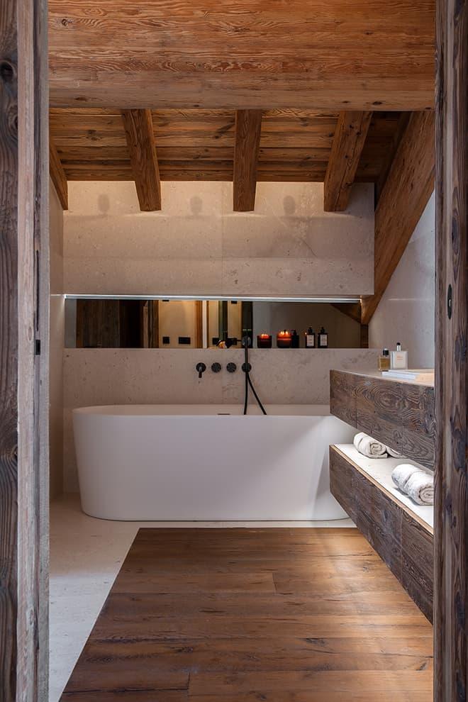 Salle de bains de la suite parentale. Baignoire îlot (Xenz). Parterre de pierre calcaire Bianco Fiorito