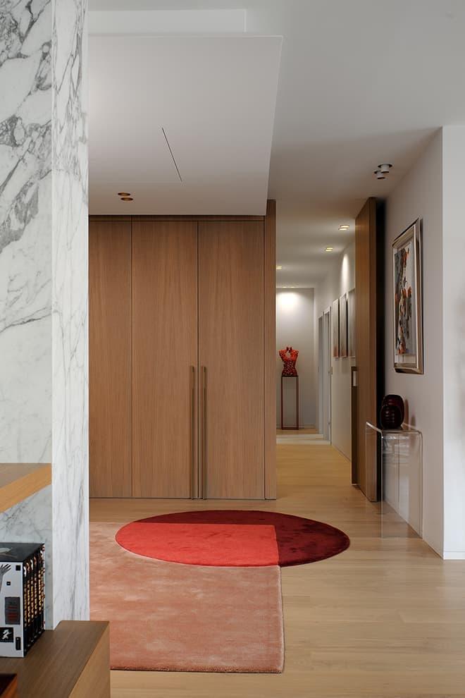 L'entrée ancre la construction verticale et horizontale sous la forme d'un agencement cousu main. Tapis (Amini). Console (Fiam Italia)
