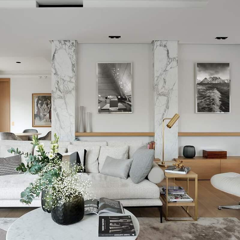 Pour habiller les piliers béton originels, le marbre Calacatta Arabesco. Canapé (B&B Italia). Fauteuil (Vitra). Tapis (Diacasan). Lampe (CTO Lighting)