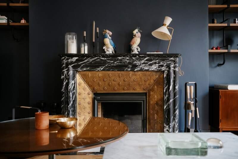 Créée de toute pièce, la cheminée fait la part belle au marbre nero, travaillé style Art déco, avec contrecœur en laiton martelé