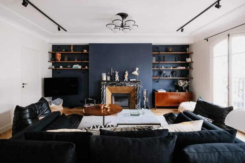 Le salon, comme toile de fond, scénarisant les objets et le mobilier chinés, sans les éclipser. Lustre (Gino Sarfati – Astep). Éclairage architectural (Wever&Ducré)