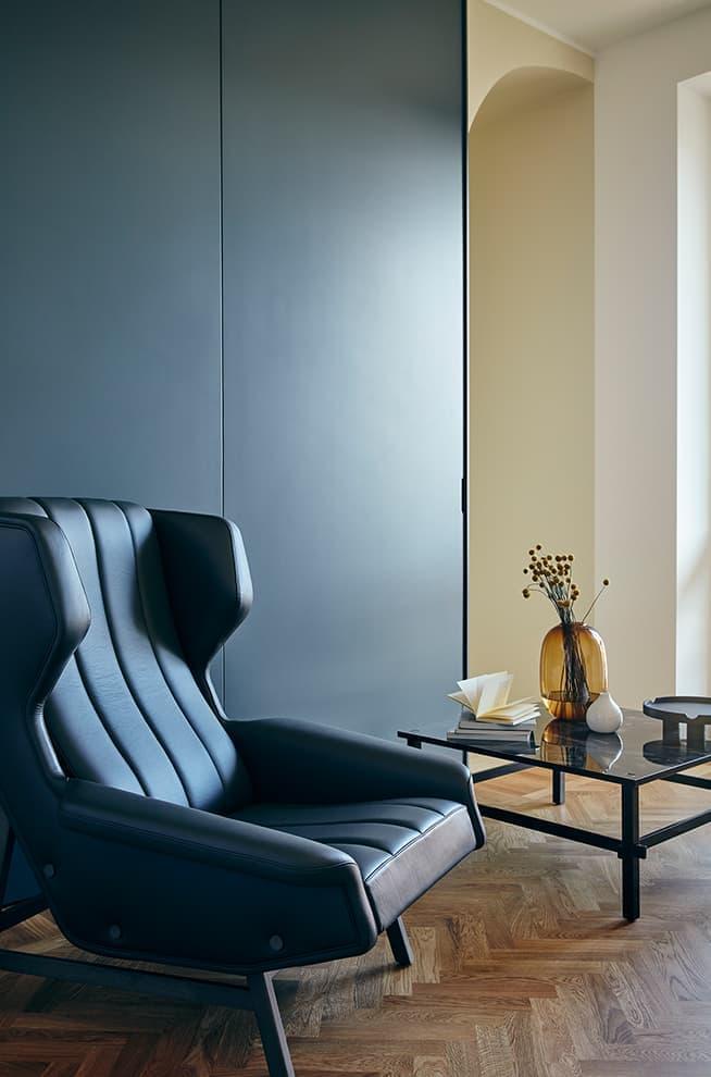 Le bureau possède deux entrées marquées d'une demi-arche et peut être refermé grâce à des panneaux coulissants. Fauteuil Giulia et table basse Gio (Tacchini)