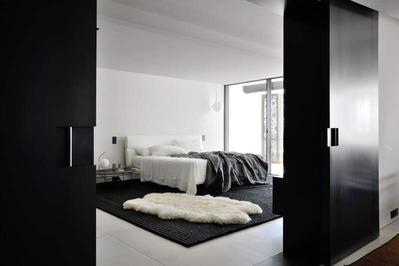 La master suite, digne de ce nom, est délimitée par des portes coulissantes XXL, en verre laqué noire, dégageant une ouverture de près de 2 mètres
