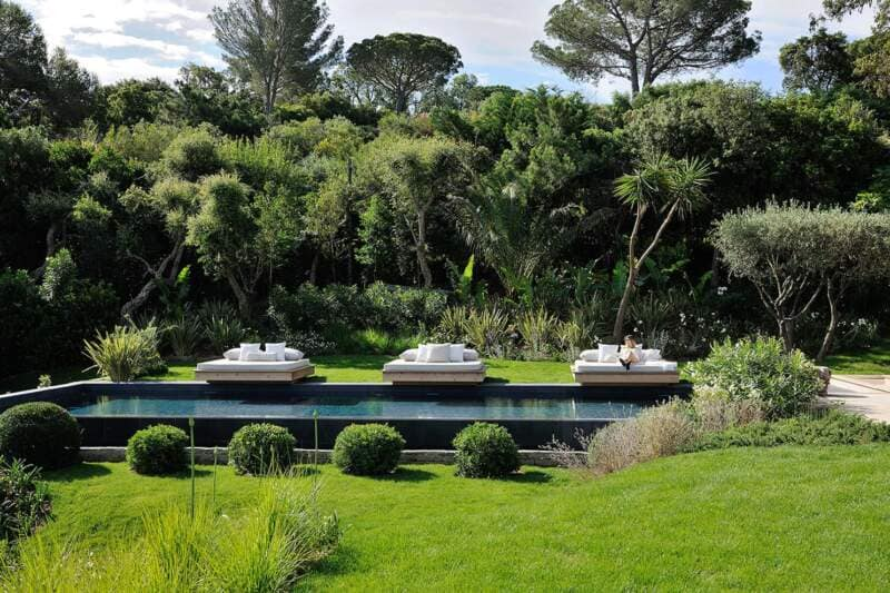 La piscine à débordement s'aligne sur l'horizon panoramique et s'inscrit dans l'aménagement paysager foisonnant, intégrant des banquettes suspendues au ras de la ligne d'eau dessinées sur-mesure