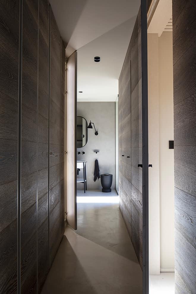 Au même étage, la master suite se cache derrière un mur habillé d'un revêtement naturel et une porte sur-mesure, dérobée au fil du mur s'ouvrant sur le dressing conçu sur-mesure