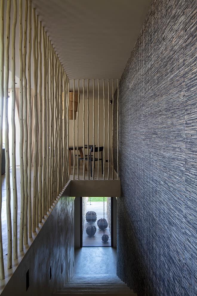 Dans la montée d'escalier reliant le salon aux chambres, revêtement naturel (Élitis) faisant face au garde-corps travaillé en échalas de châtaigner