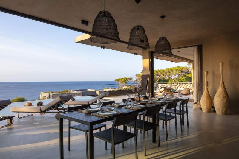 Les frontières entre espaces intérieurs et extérieurs sont gommées dans la salle à manger d'été par l'enduit nuancé kaki et le sol en béton