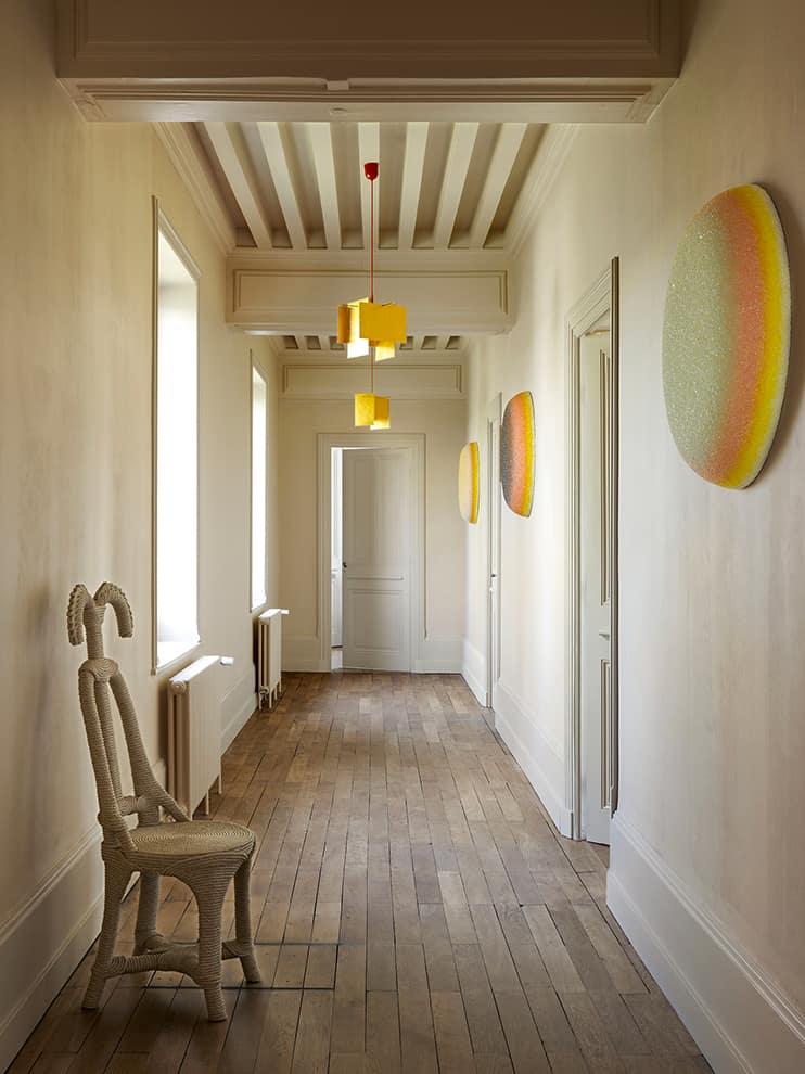 Au deuxième étage, les plafonds à la française sont animés par les ocelles de Vincent Beaurin, en verre pailleté. Chaise Moiste de Christian Astuguevieille (Galerie Zebres). Suspension 24 Karat Blau (Ingo Maurer)