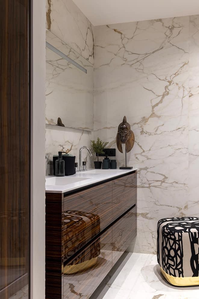 Dans la salle de bains, l'ébène de Macassar (Modulis) contraste avec le marbre veiné. Accessoires (Design & Bain Lyon)