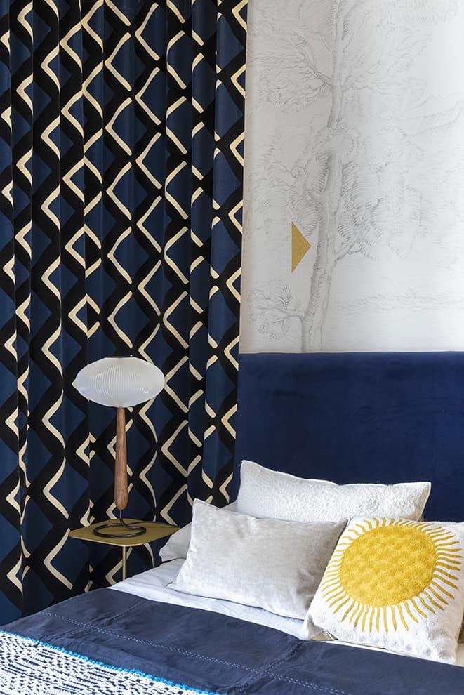 La chambre invitée se nuance de bleu sur les rideaux True Velvet (India Mahdavi – Pierre Frey) et la tête de lit en velours. Papier peint (Wall&Decó). Lampe de table L'Opulus (Rispal)