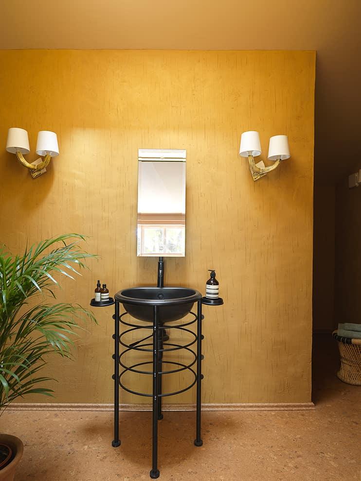 La salle de bains décuple les teintes minérales portées par l'enduit ocre griffé et le sol en liège. Vasque Lola Herzburg de Philippe Starck (Rapsel)